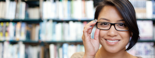 stock photo of girl smiling wearing glasses, library in background